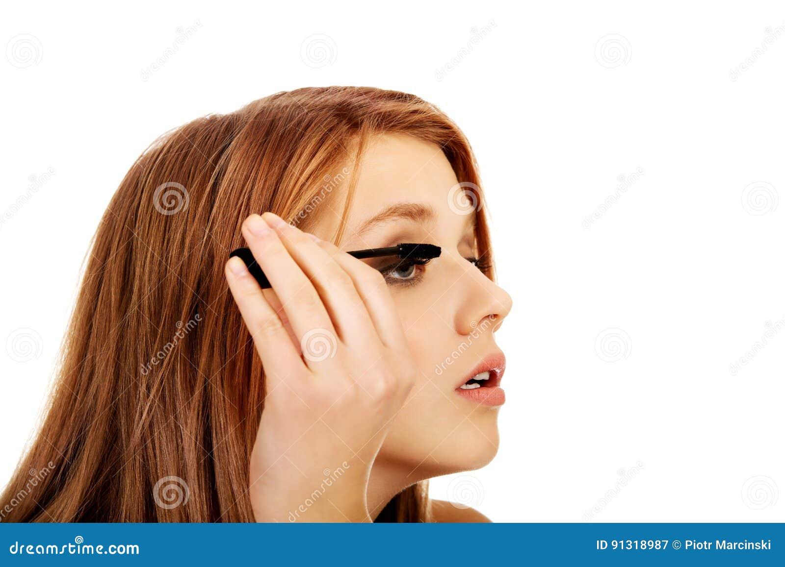 Belle femme adolescente appliquant le mascara