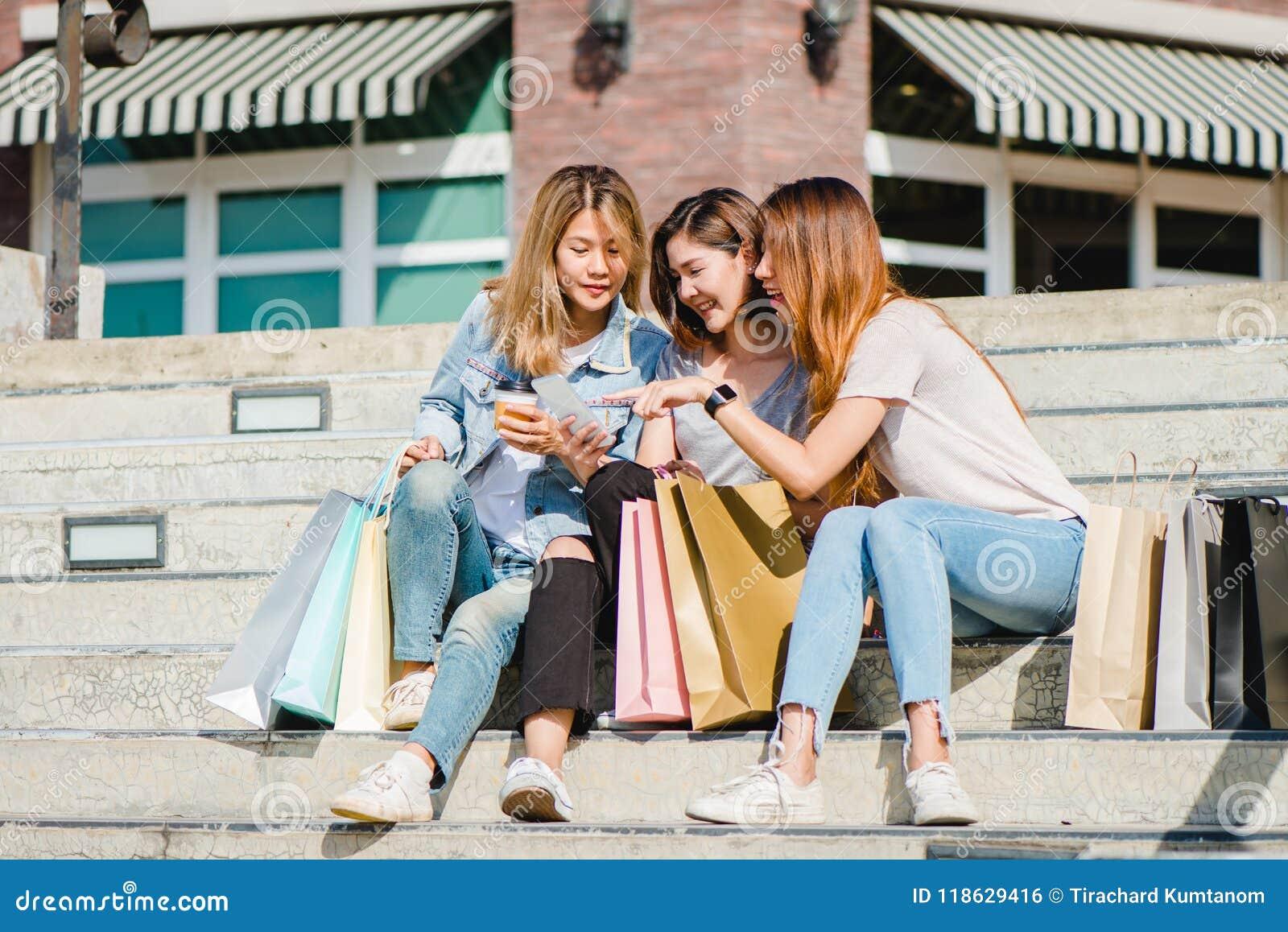 Belle femme asiatique attirante à l aide d un smartphone tout en faisant des emplettes dans la ville Jeune adolescent asiatique h