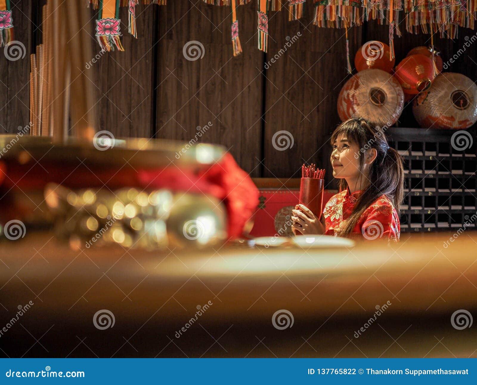 Belle femme asiatique avec l habillement de tradition tenant le cylindre en bambou des bâtons de Chi de Chi ou du Chien Tung, Cou