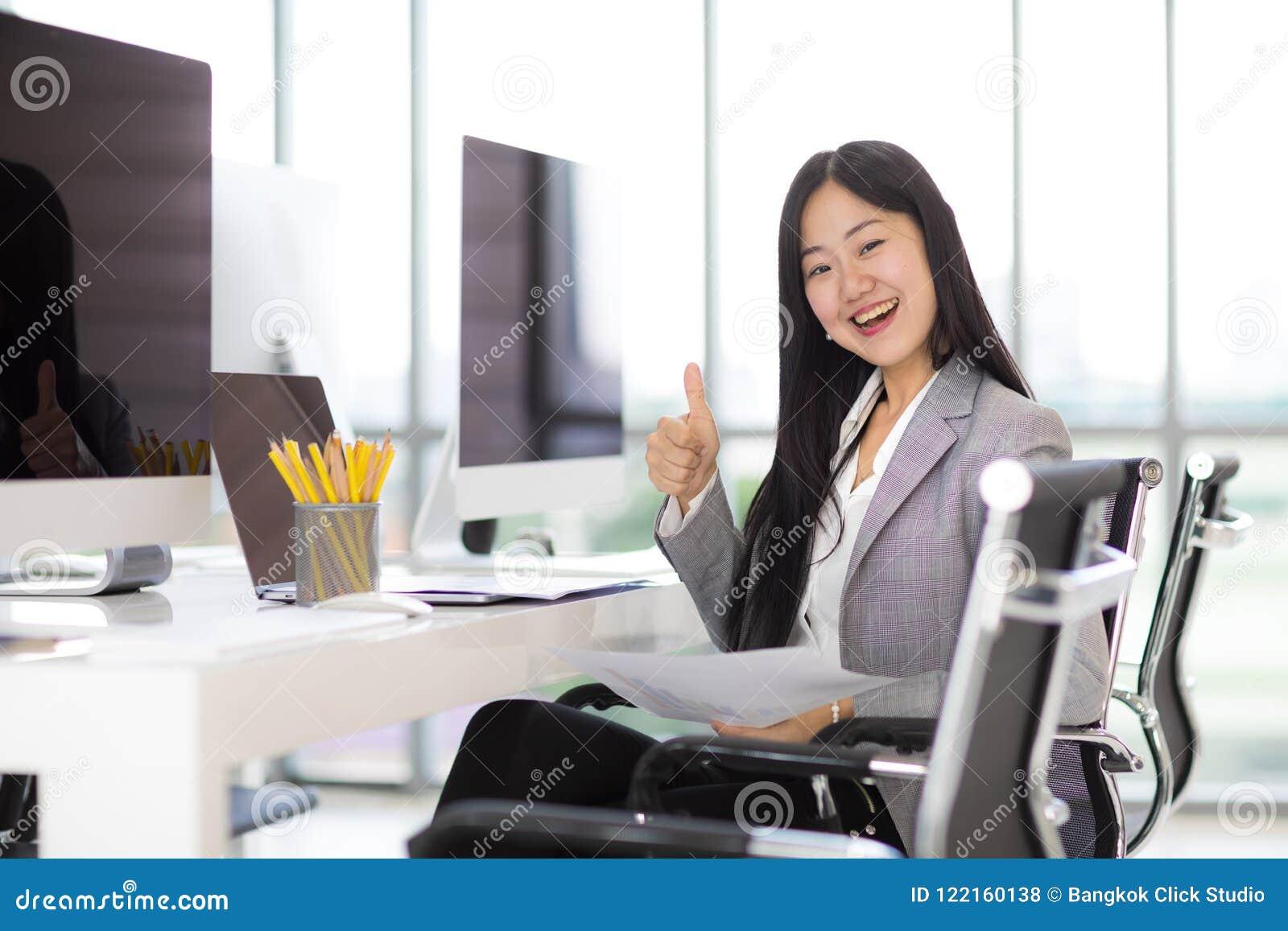 Belle femme asiatique d affaires s asseyant et souriant sur la chaise en m