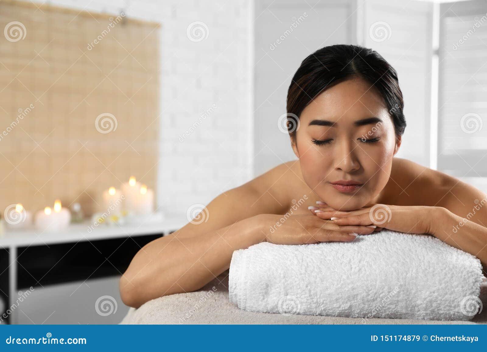 Belle femme asiatique se trouvant sur la table de massage dans le salon de station thermale