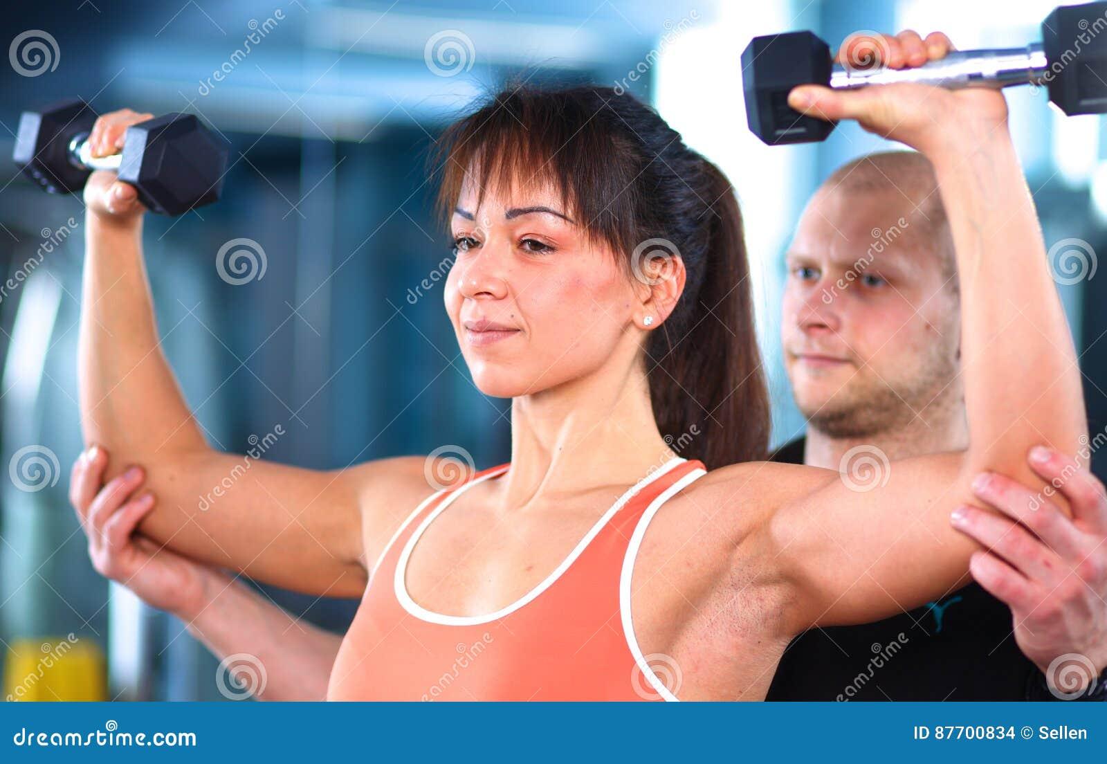 Belle femme au gymnase s exerçant avec son entraîneur