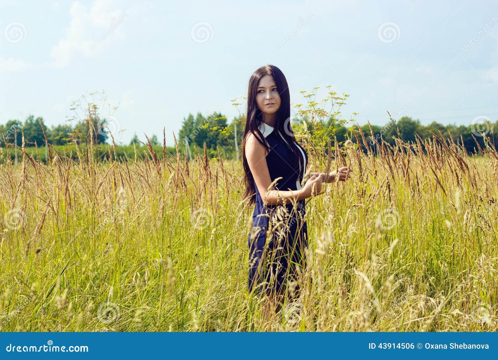 Belle femme avec de longs cheveux foncés se tenant dans le champ de maïs ensoleillé
