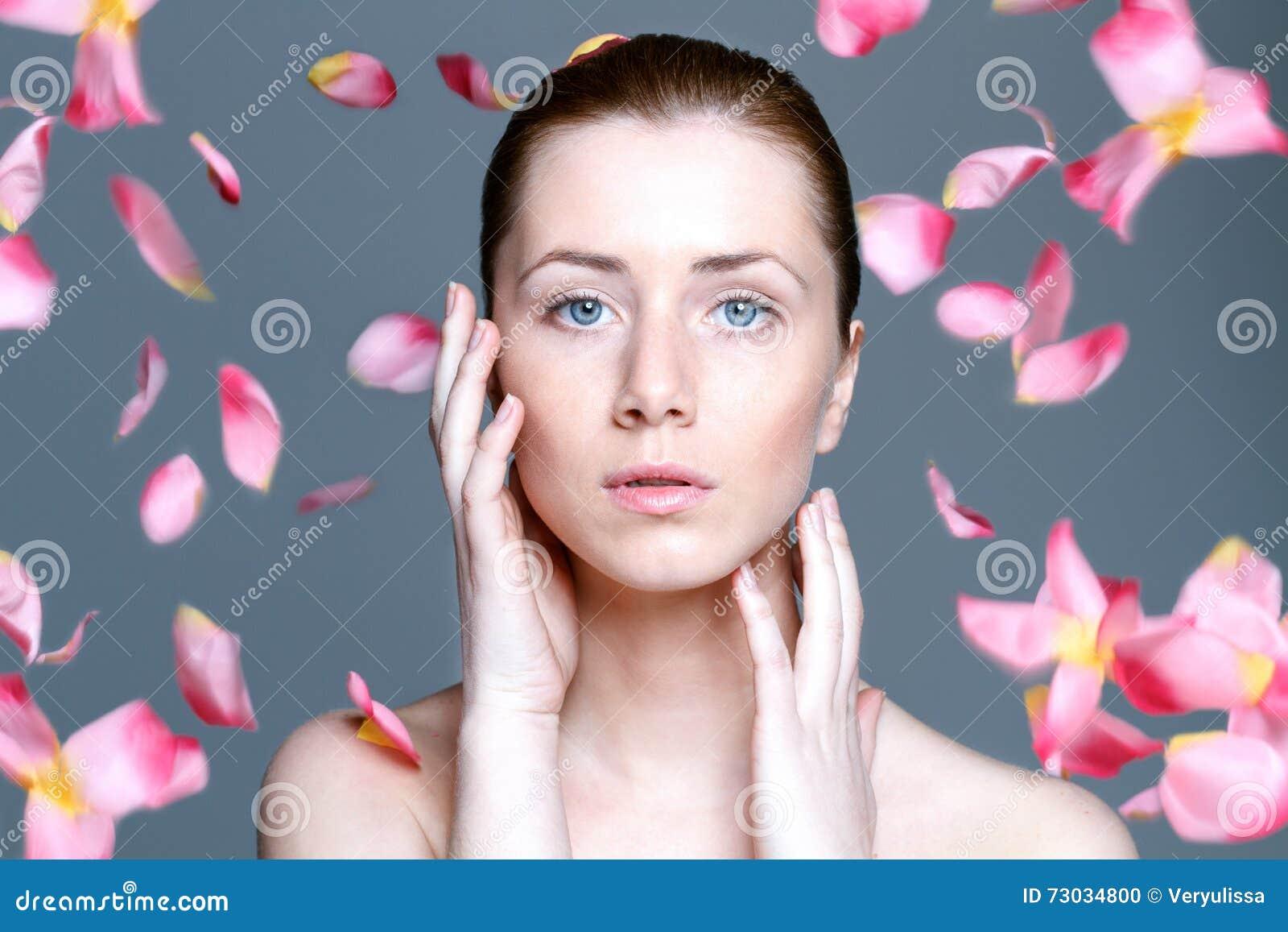 Belle femme avec la peau claire et les pétales de rose en baisse