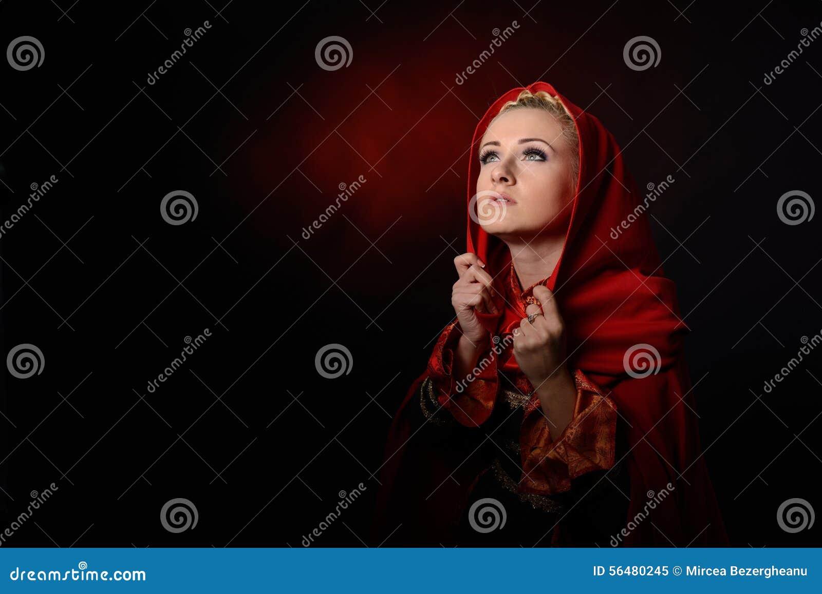 Belle femme avec le manteau rouge dans le studio
