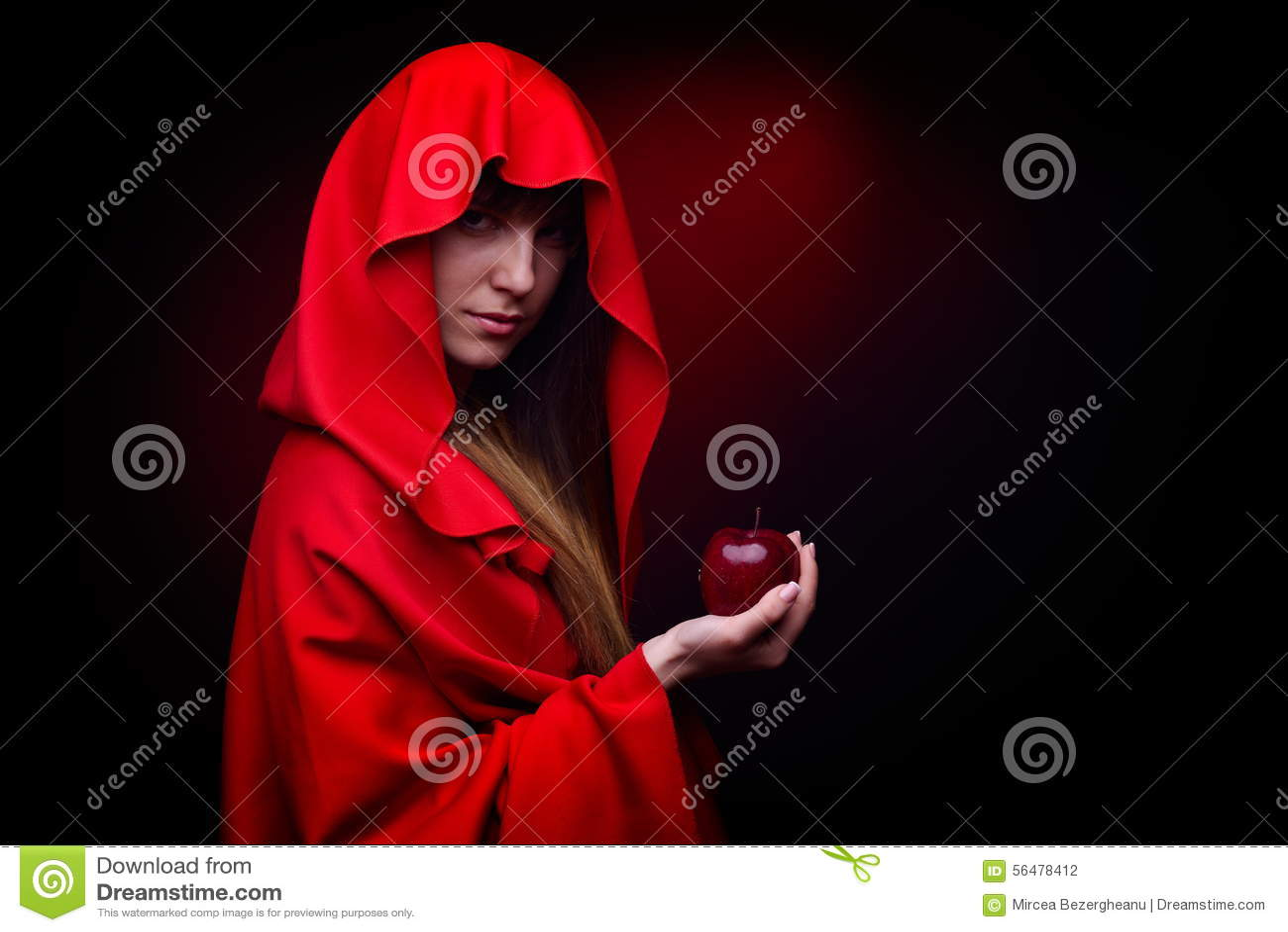 Belle femme avec le manteau rouge tenant la pomme