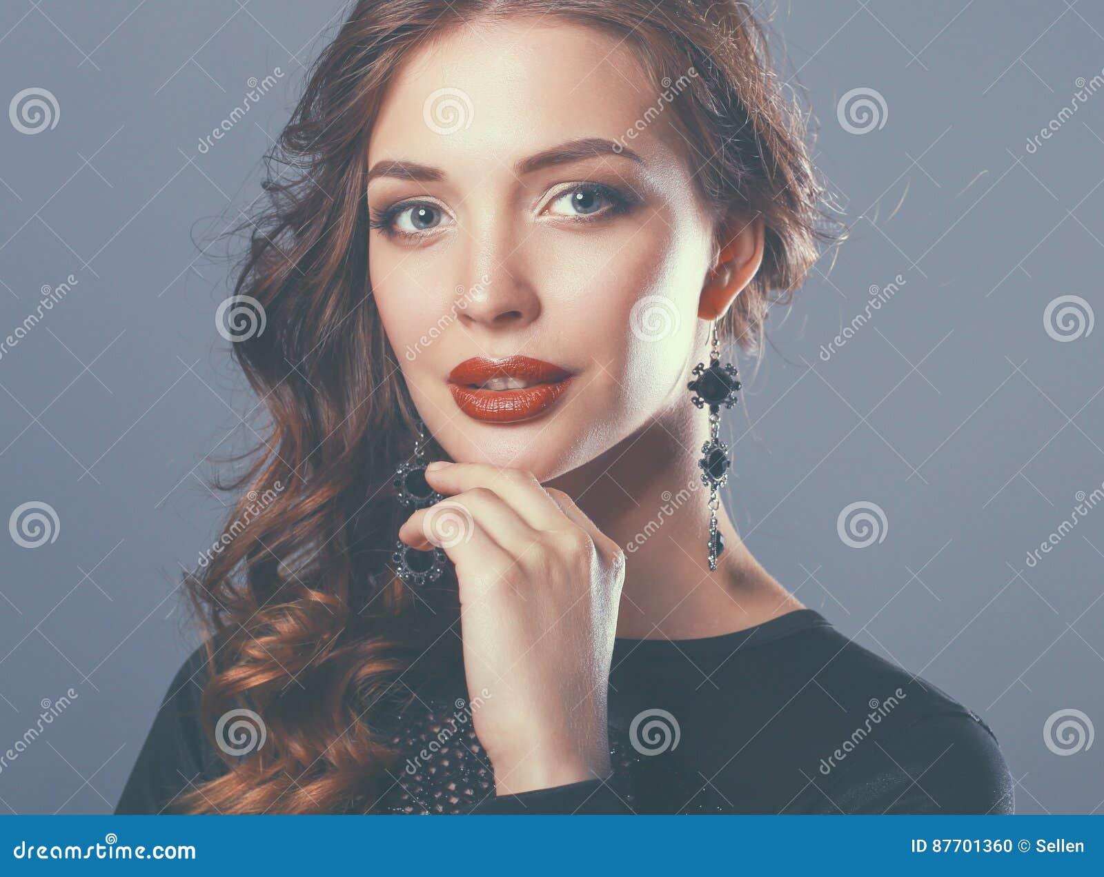 Belle femme avec le maquillage de soirée dans la robe noire