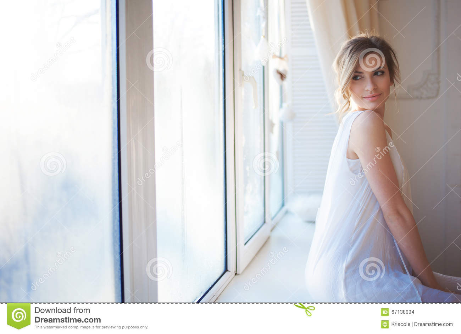 Belle femme avec le maquillage quotidien frais et la coiffure onduleuse romantique, se reposant au rebord de fenêtre