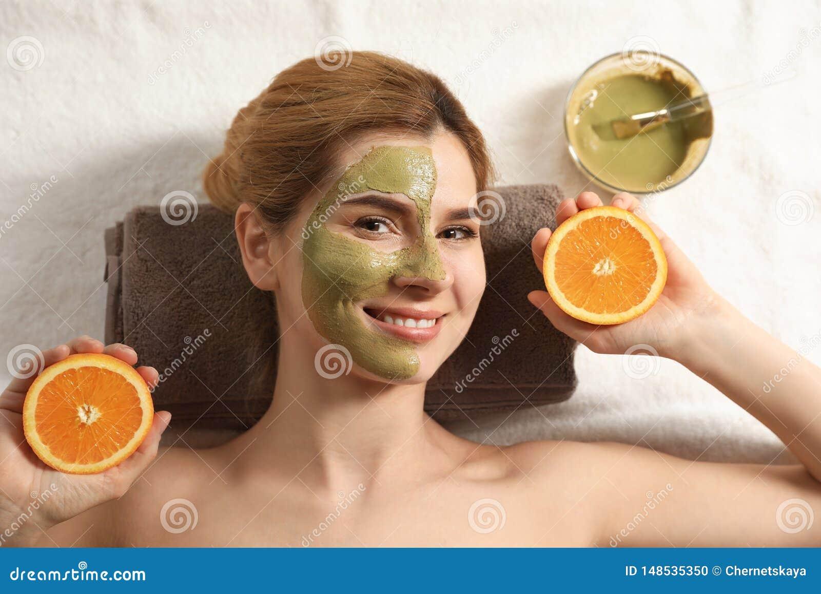 Belle femme avec le masque sur le visage et couper la détente orange