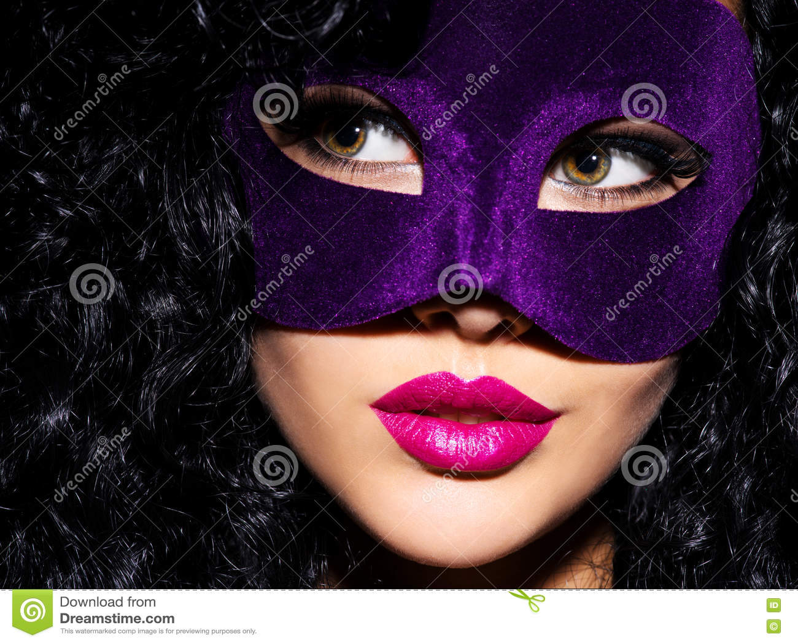 Belle femme avec les poils noirs et masque violet de théâtre sur le fac