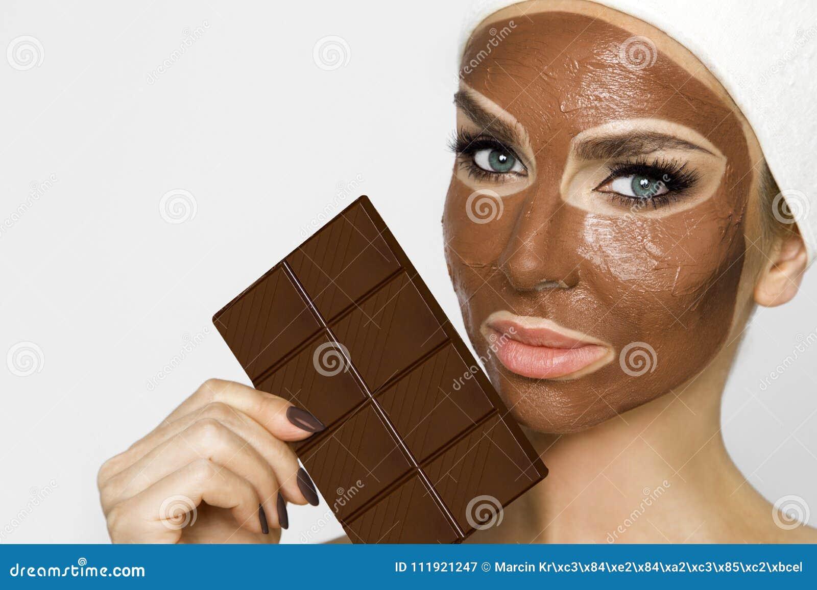 Belle femme blonde avec un masque facial, station thermale de beauté Masque protecteur de chocolat
