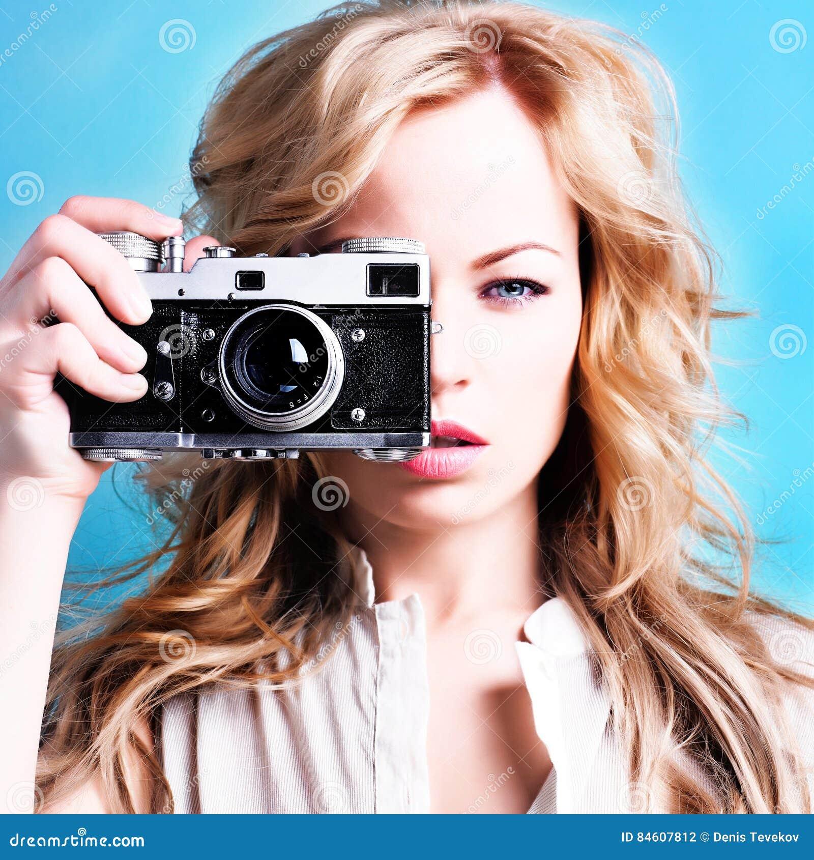 Belle femme blonde de photographe tenant le rétro appareil-photo