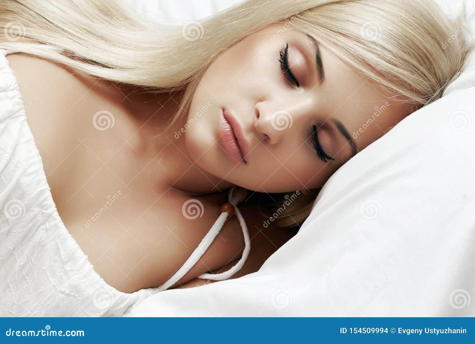 Belle femme blonde de sommeil dans le lit