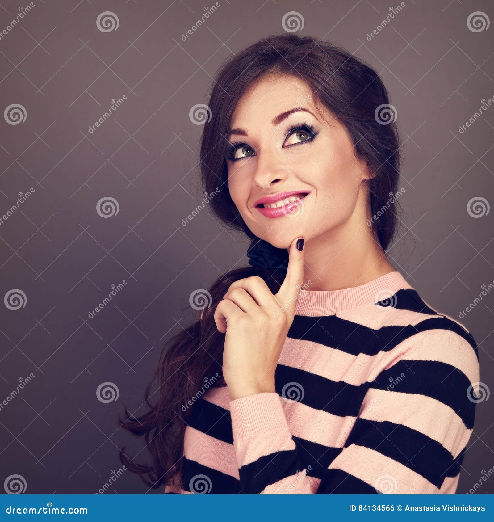 Belle femme bouclée occasionnelle de pensée de coiffure recherchant avec