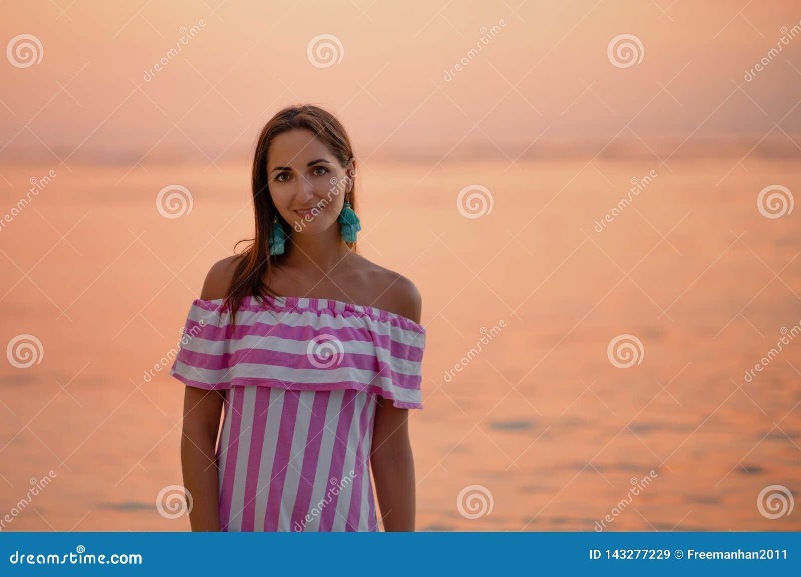 Belle femme bronz?e dans la robe avec les rayures blanches et roses Fermez-vous et copiez l espace Mer ou oc?an orange au coucher