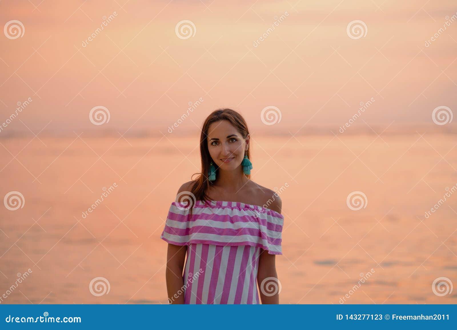 Belle femme bronz?e dans la robe avec les rayures blanches et roses Mer ou oc?an orange au coucher du soleil Vacations le concept