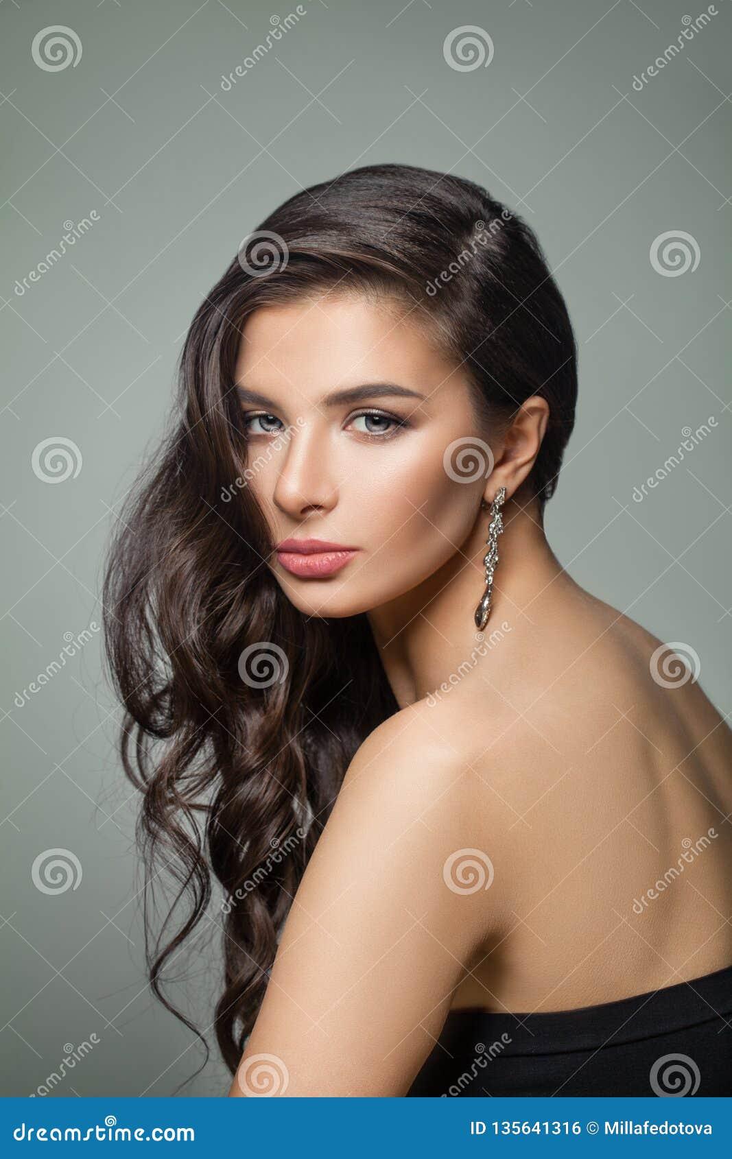 Belle femme brune foncée de cheveux Mannequin avec la longs coiffure, maquillage et boucles d oreille parfaits de bijoux