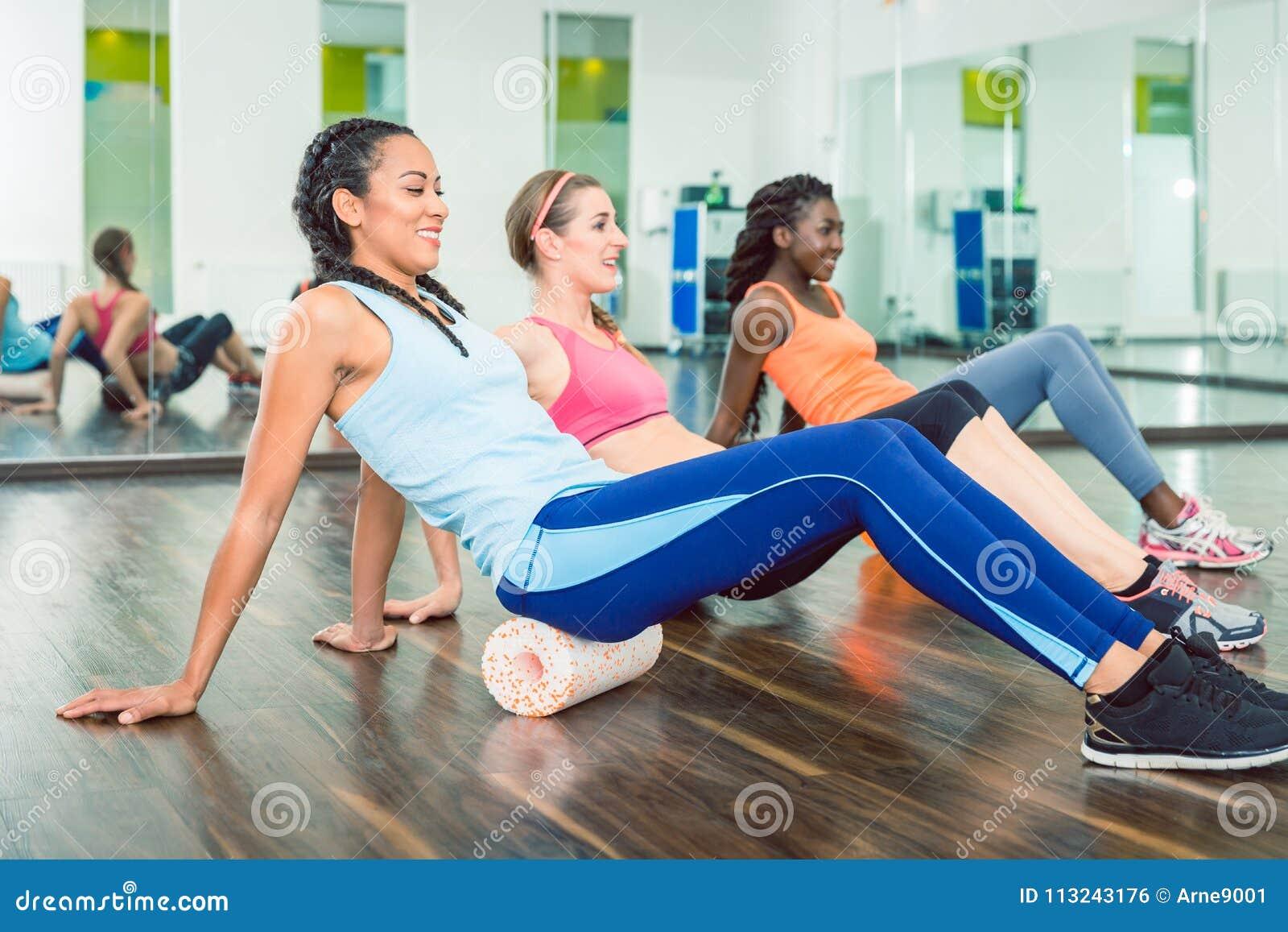 Belle femme convenable s exerçant sur le rouleau de mousse pendant la classe de séance d entraînement de groupe
