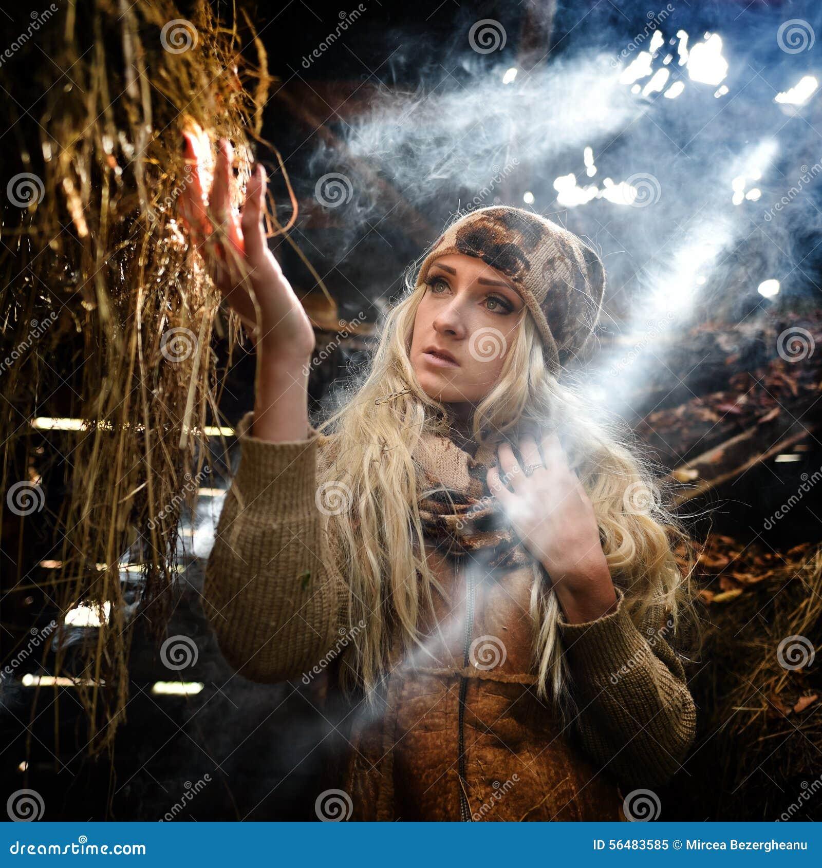 Belle femme détendant en paille en automne dans la chambre fumeuse