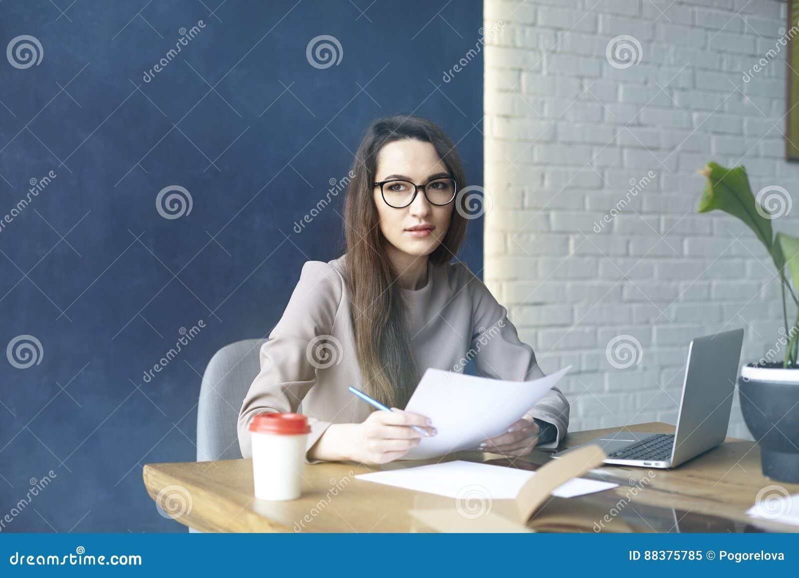 Belle femme d affaires avec de longs cheveux fonctionnant avec la documentation, feuille, ordinateur portable tout en se reposant