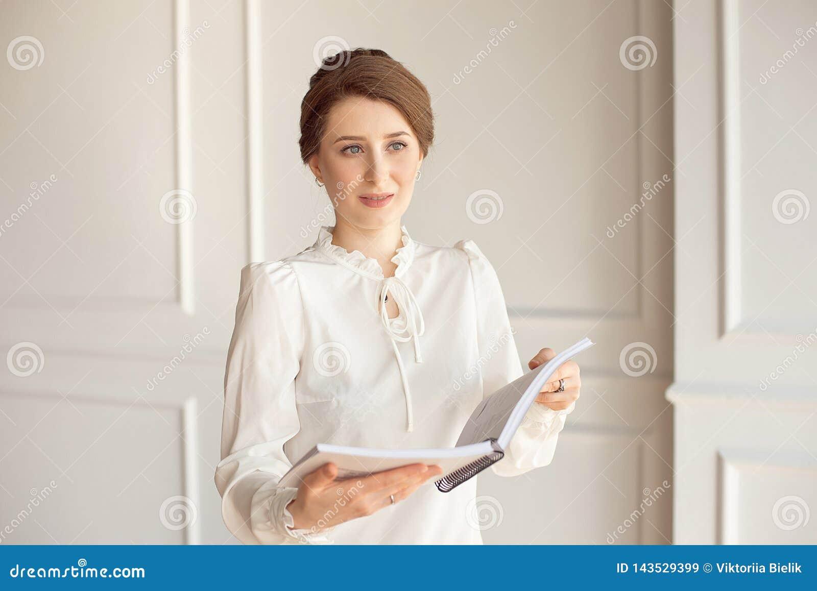 Belle femme d affaires dans une chemise blanche et un pantalon foncé tenant un dossier avec des documents