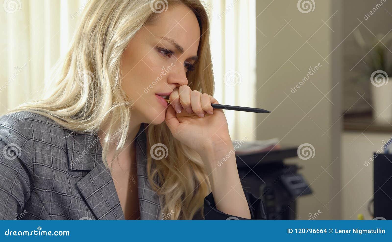 Belle femme d affaires mordant son crayon dans le bureau