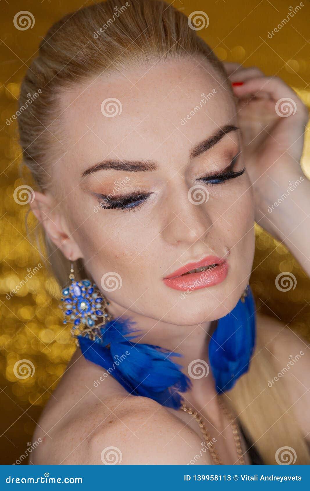 Belle femme d or de mode, modèle avec de longs cheveux sains brillants de volume Coiffure de volume d updo de boucles de vagues S