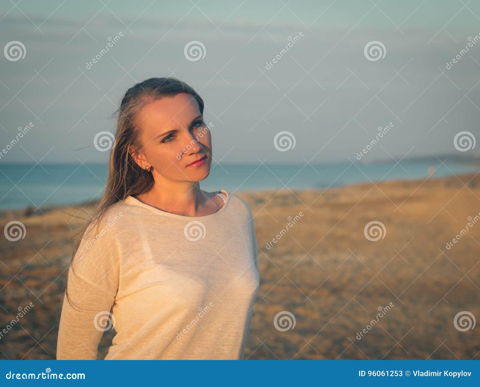 Belle femme dans la chemise blanche à la plage de soirée