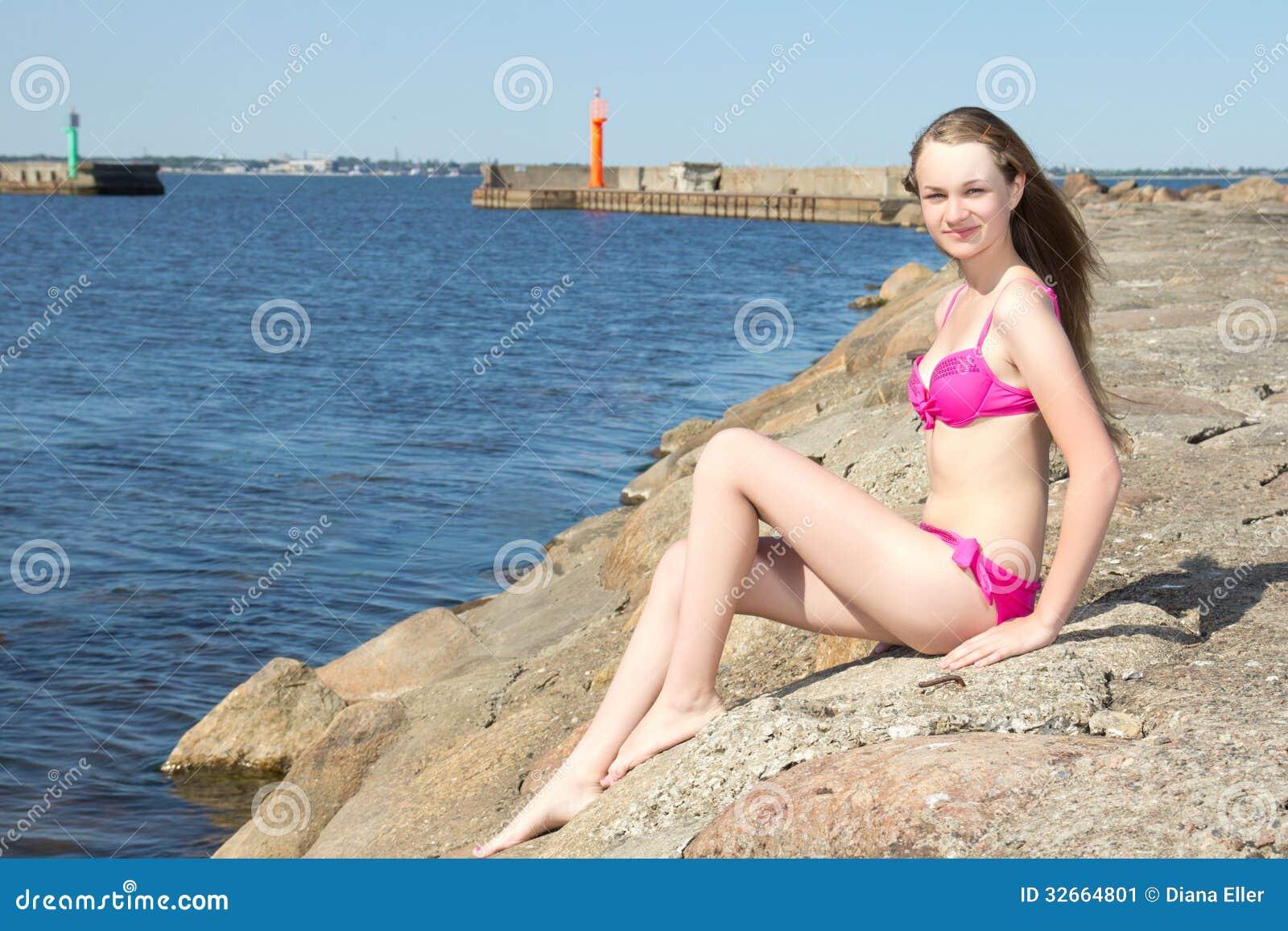 Belle femme dans le bikini rose se reposant sur la plage rocheuse image stock image 32664801 - Sortie de plage femme ...