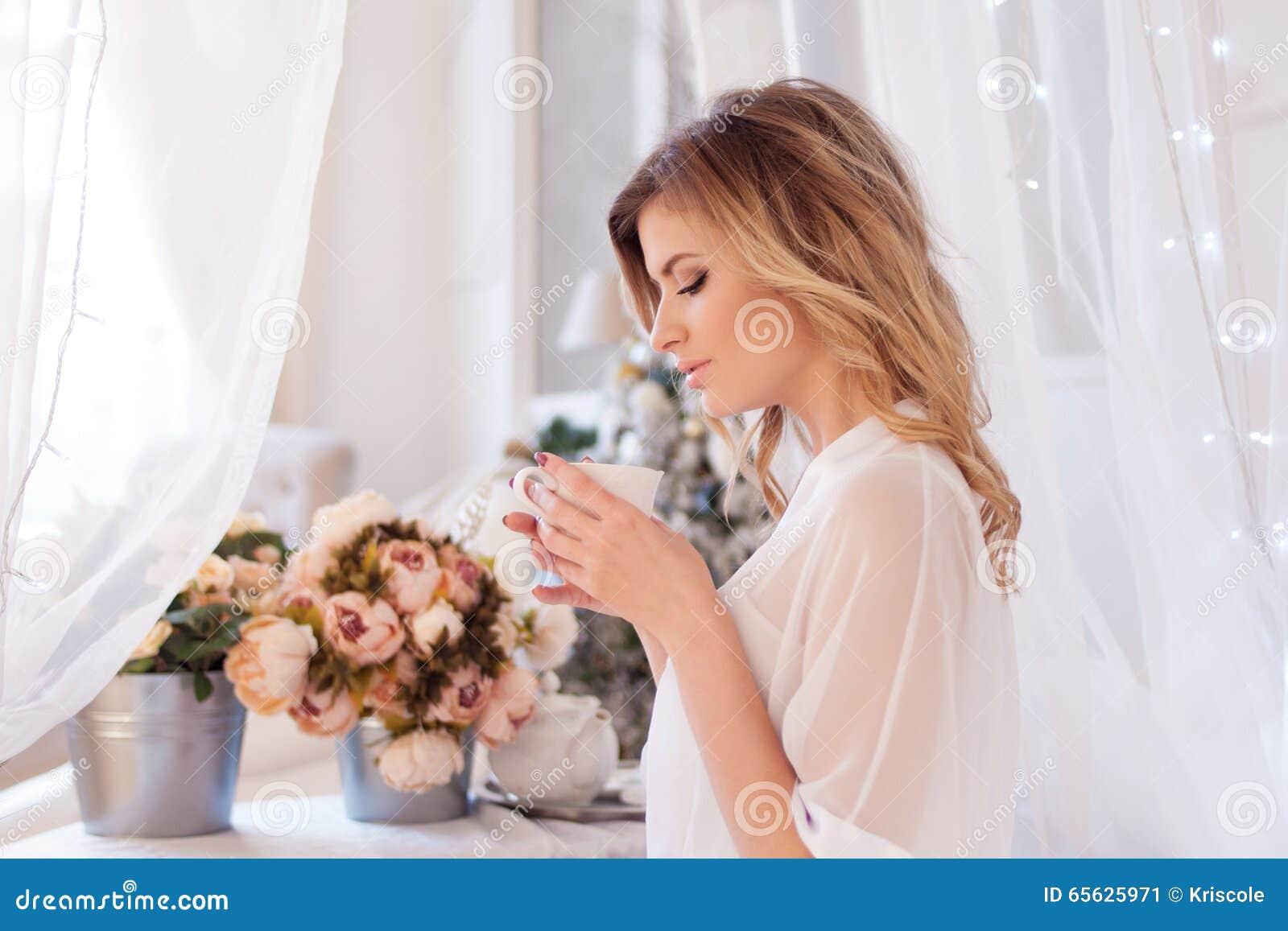 Belle femme dans le café potable de chambre à coucher Une fille tient la tasse, apprécient une boisson