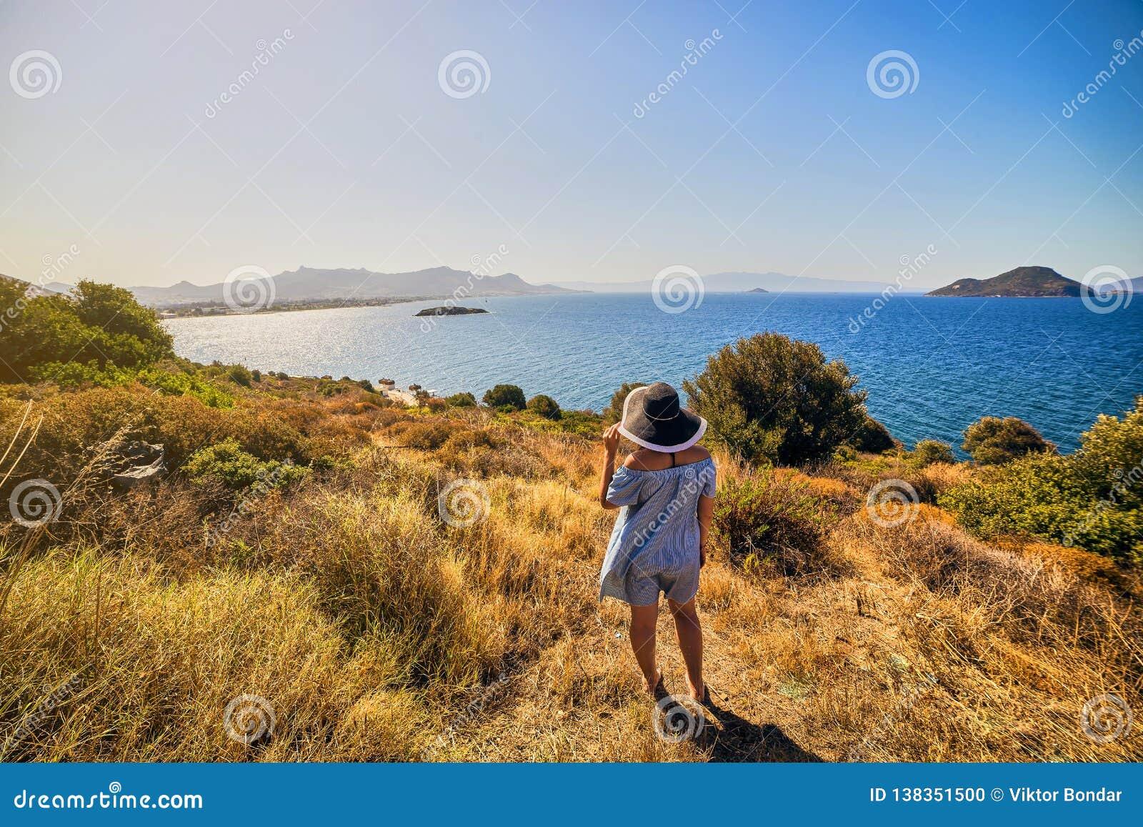 Belle femme dans le chapeau de plage appréciant la vue de mer avec le ciel bleu au jour ensoleillé dans Bodrum, Turquie Été de pa