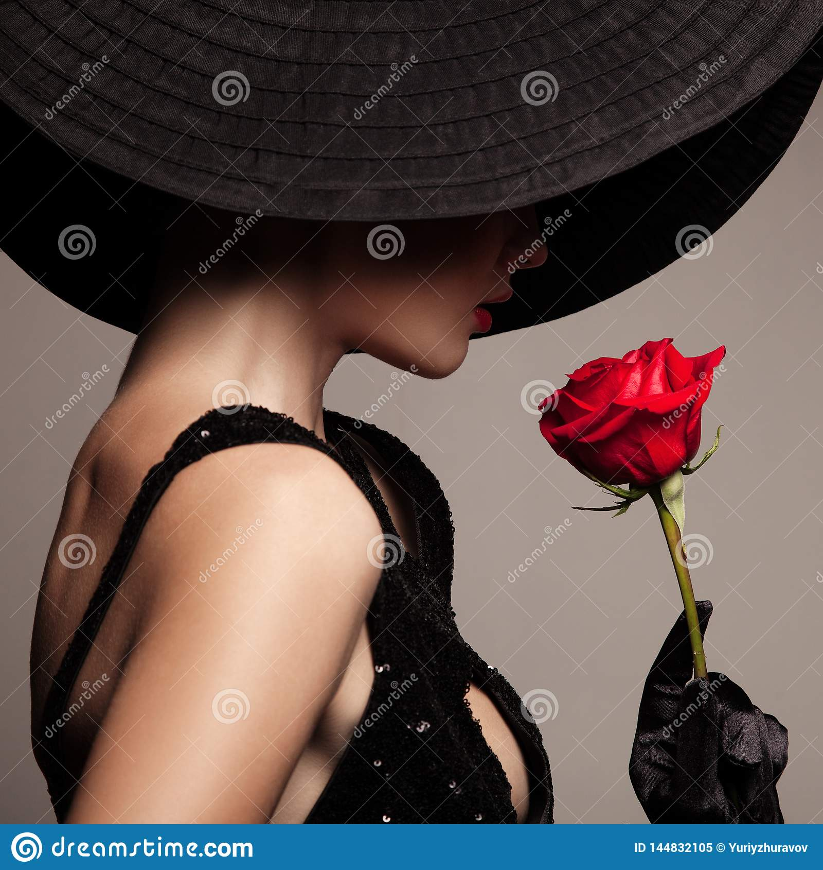 Belle femme dans le chapeau noir et la rose rouge