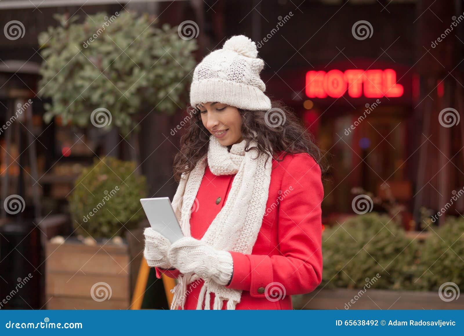Belle femme dans le chapeau rouge de manteau et de laine et gants avec le smartph
