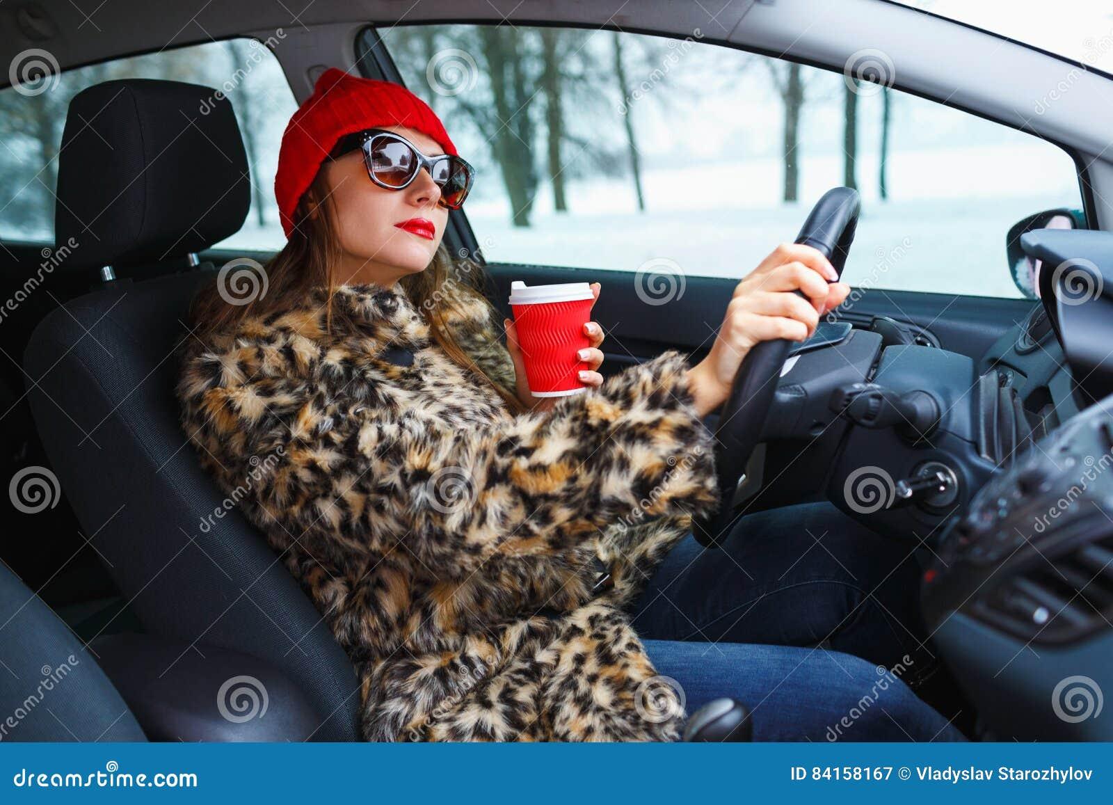Belle femme dans un manteau de fourrure et un chapeau rouge avec du café à aller driv
