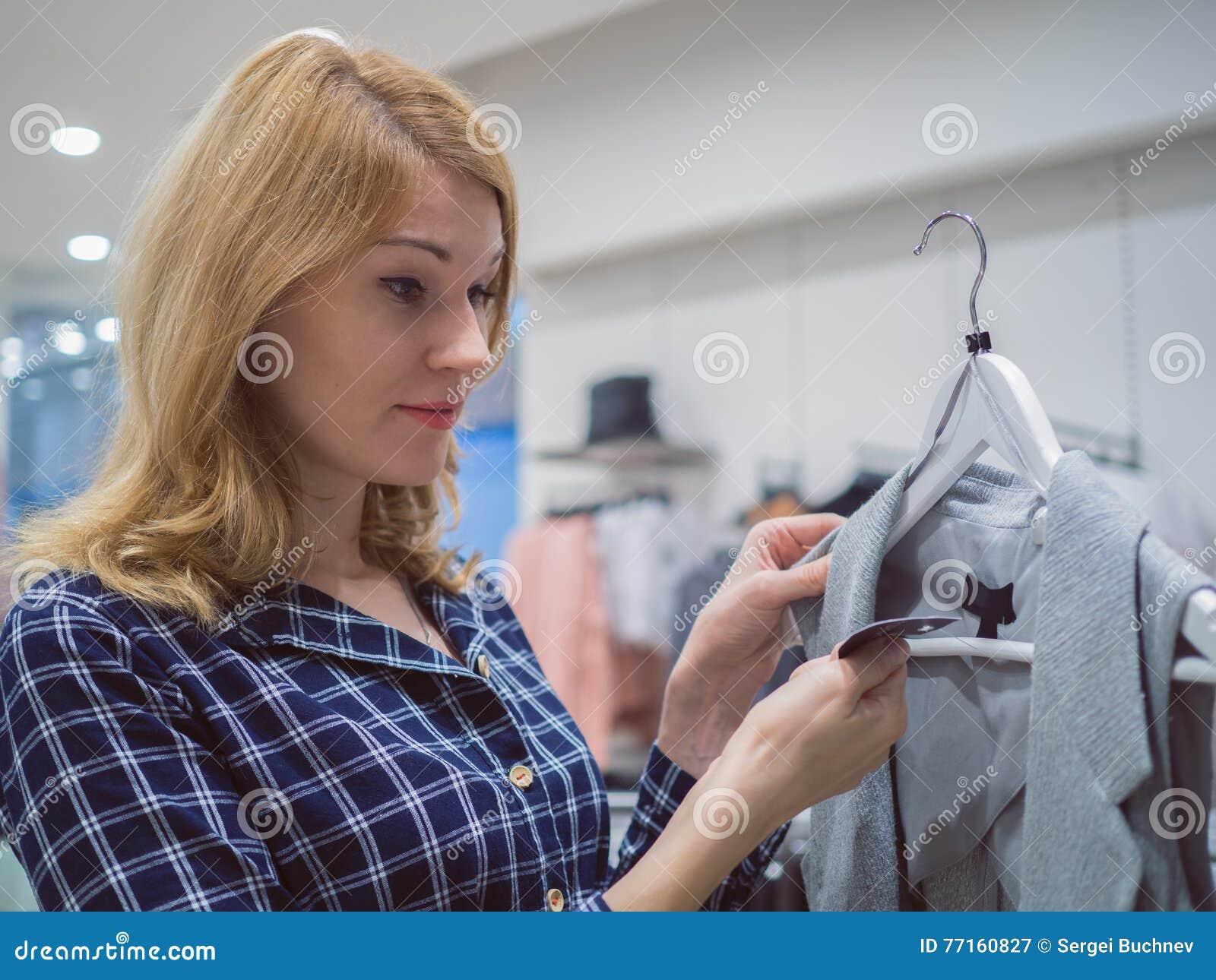 Belle femme dans une boutique d habillement La fille blonde choisit l ennui