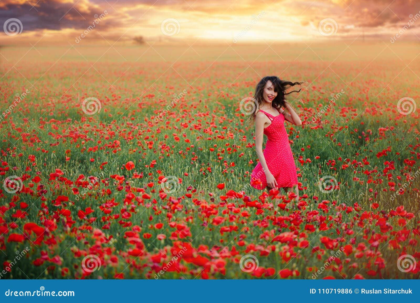 Belle femme dans une robe rouge dans un domaine de pavot aux cheveux de flottement de coucher du soleil, à la tonalité chaude, au