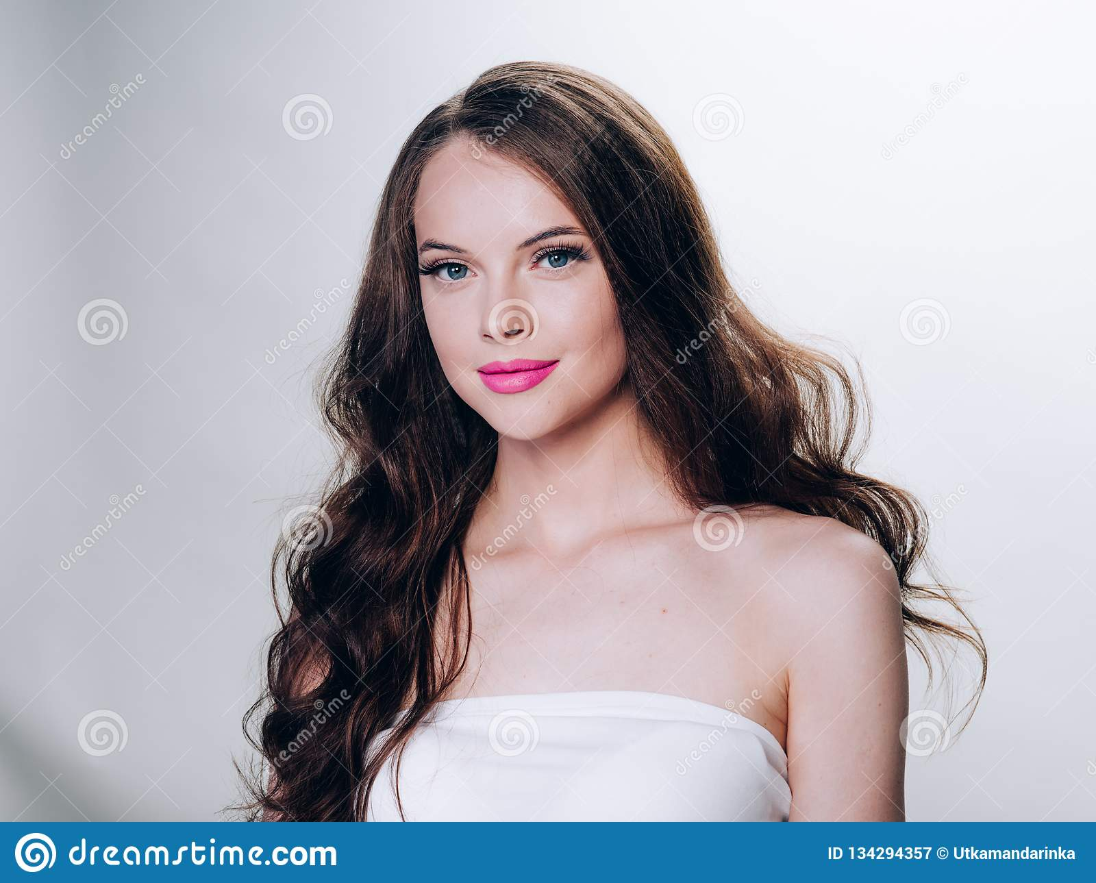 Belle femme de brune avec le rouge à lèvres bouclé de rose de coiffure d extension de cils et de longue brune