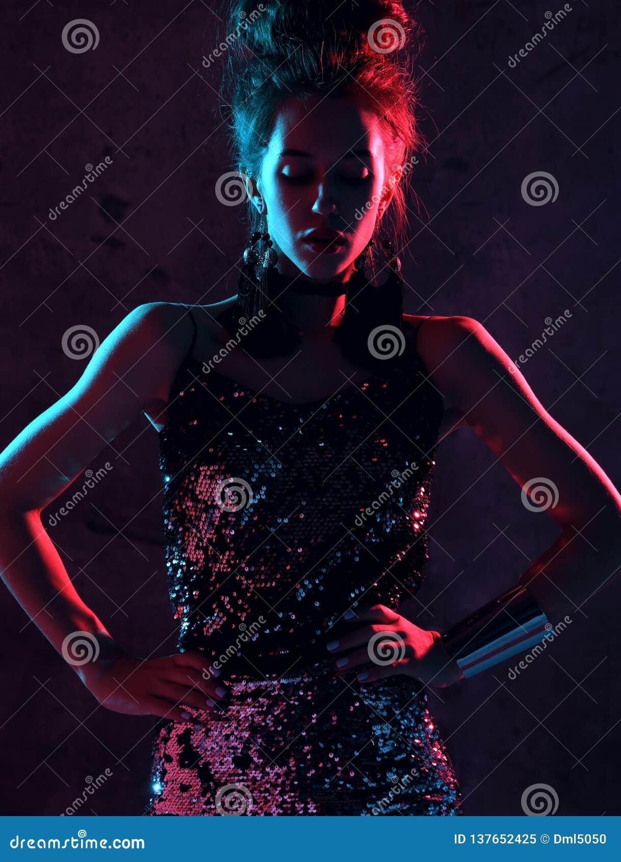 Belle femme de brune de mode posant dans la lampe au néon bleue et rose dans la robe d étincelle d or de mode sur l obscurité