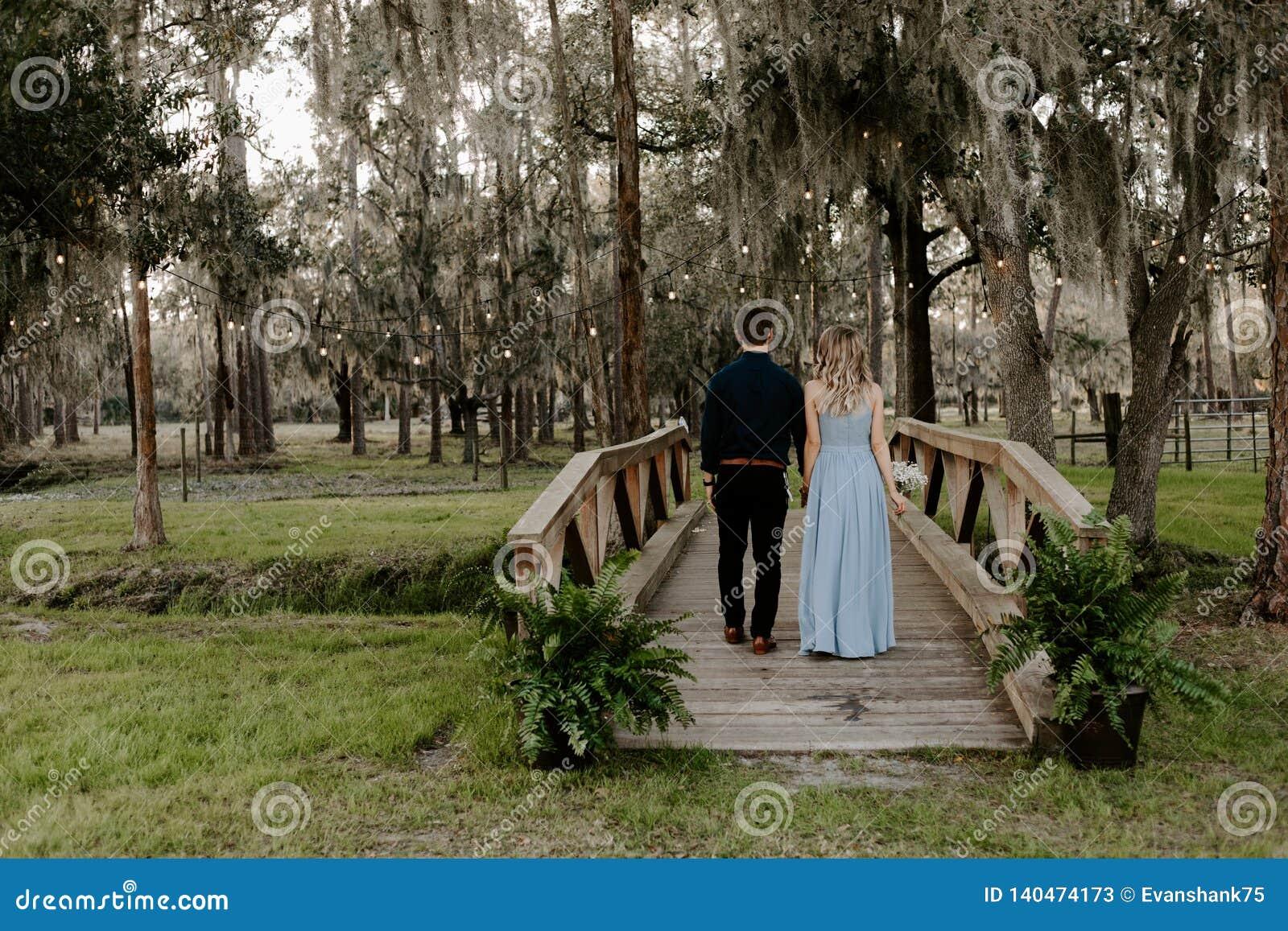 Belle femme de demoiselle d honneur dans la robe bleue et bouquet avec sa date à un événement formel de célébration de noce dehor