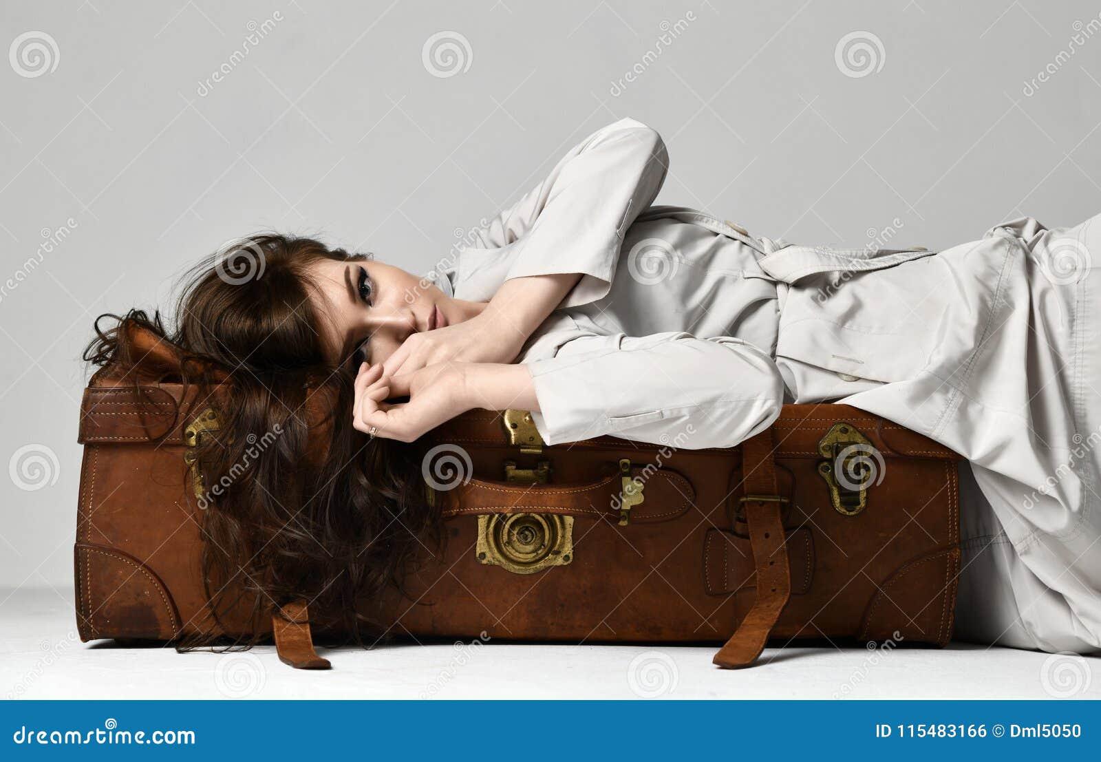 Belle femme de hippie de brune dans la veste grise d automne se trouvant sur le rétro sac brun en cuir de voyage sur le gris