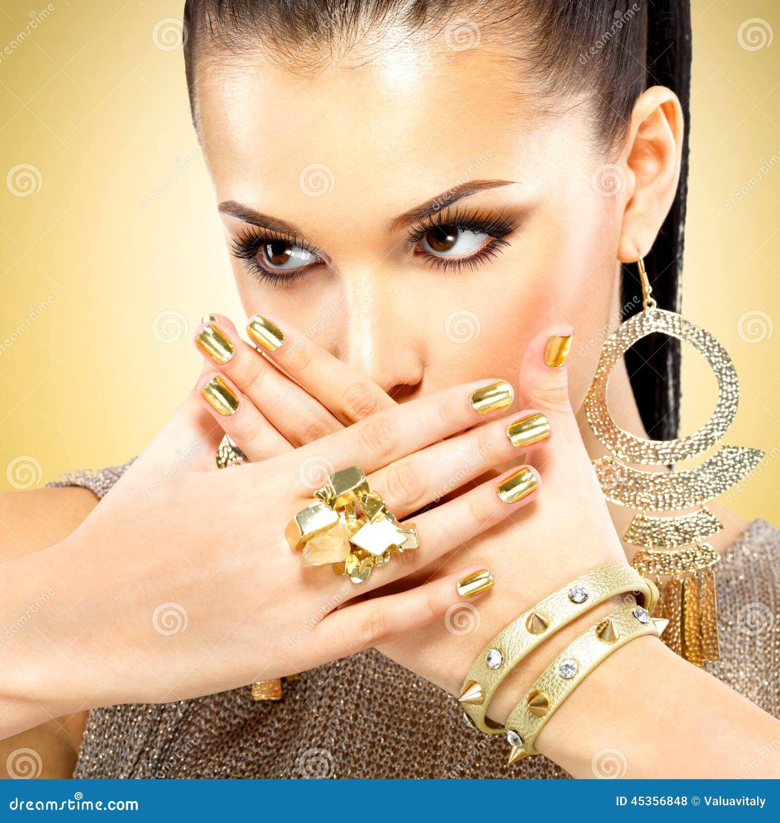 Belle femme de mode avec le maquillage noir et la manucure d or