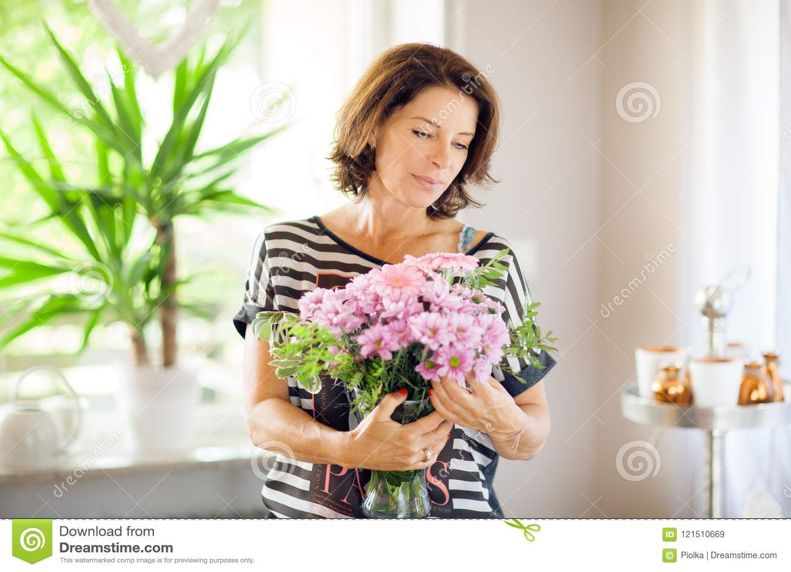 Belle femme de Moyen Âge décorant à la maison des fleurs