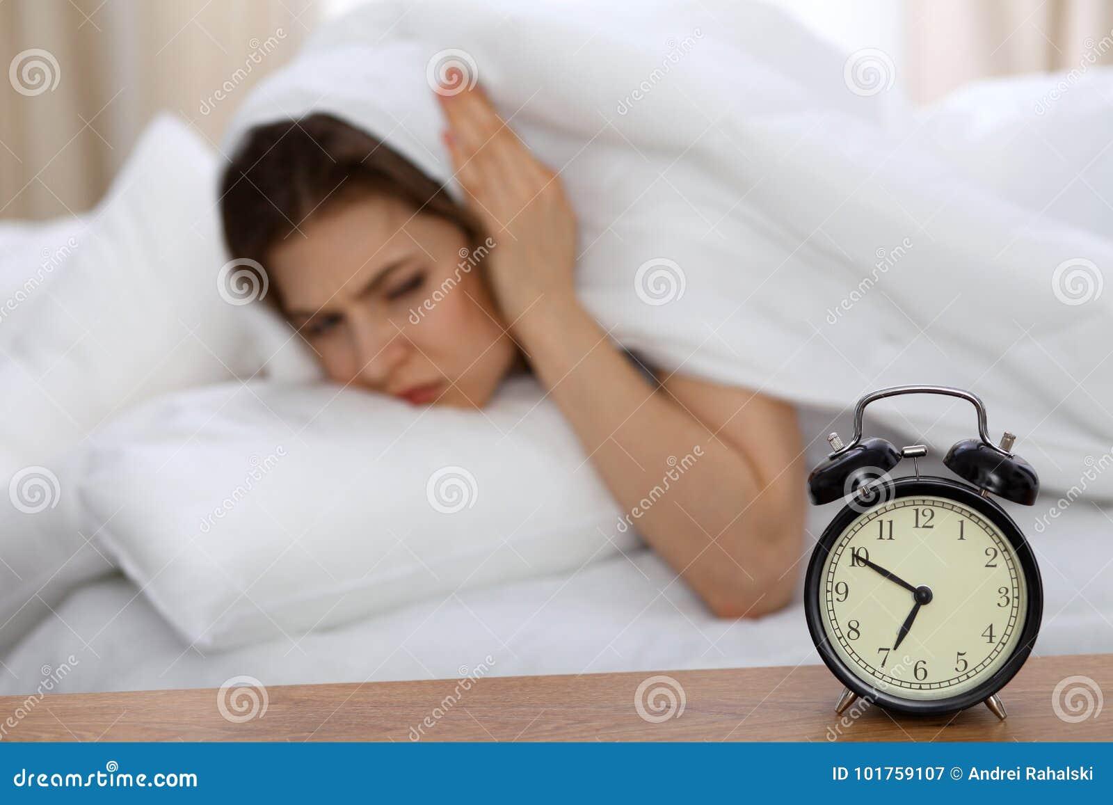 Belle femme de sommeil se situant dans le lit et essayant de se réveiller avec le réveil Fille ayant des ennuis avec se lever tôt