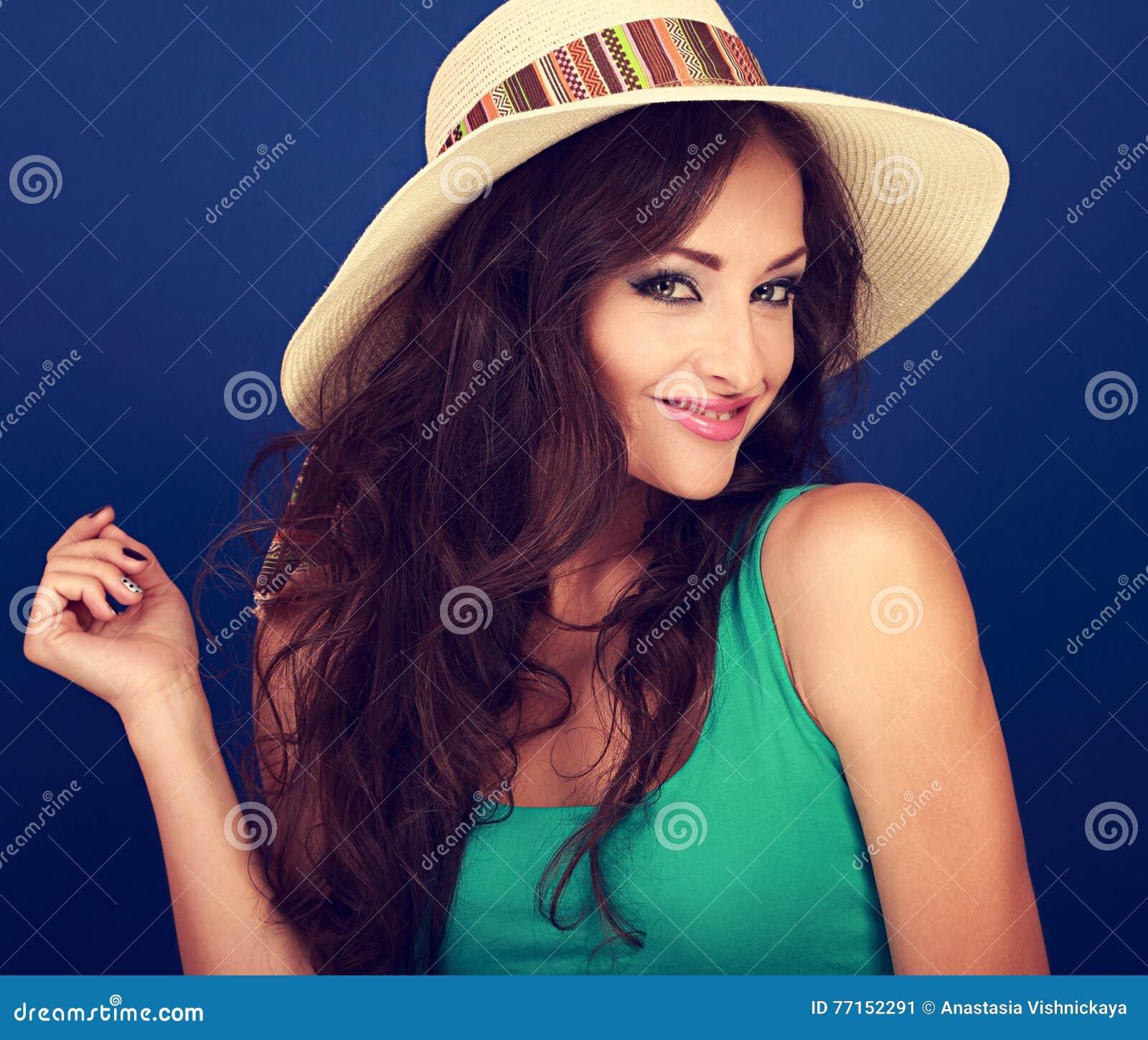 Belle femme de sourire dans le chapeau d été avec de longs cheveux bruns bouclés