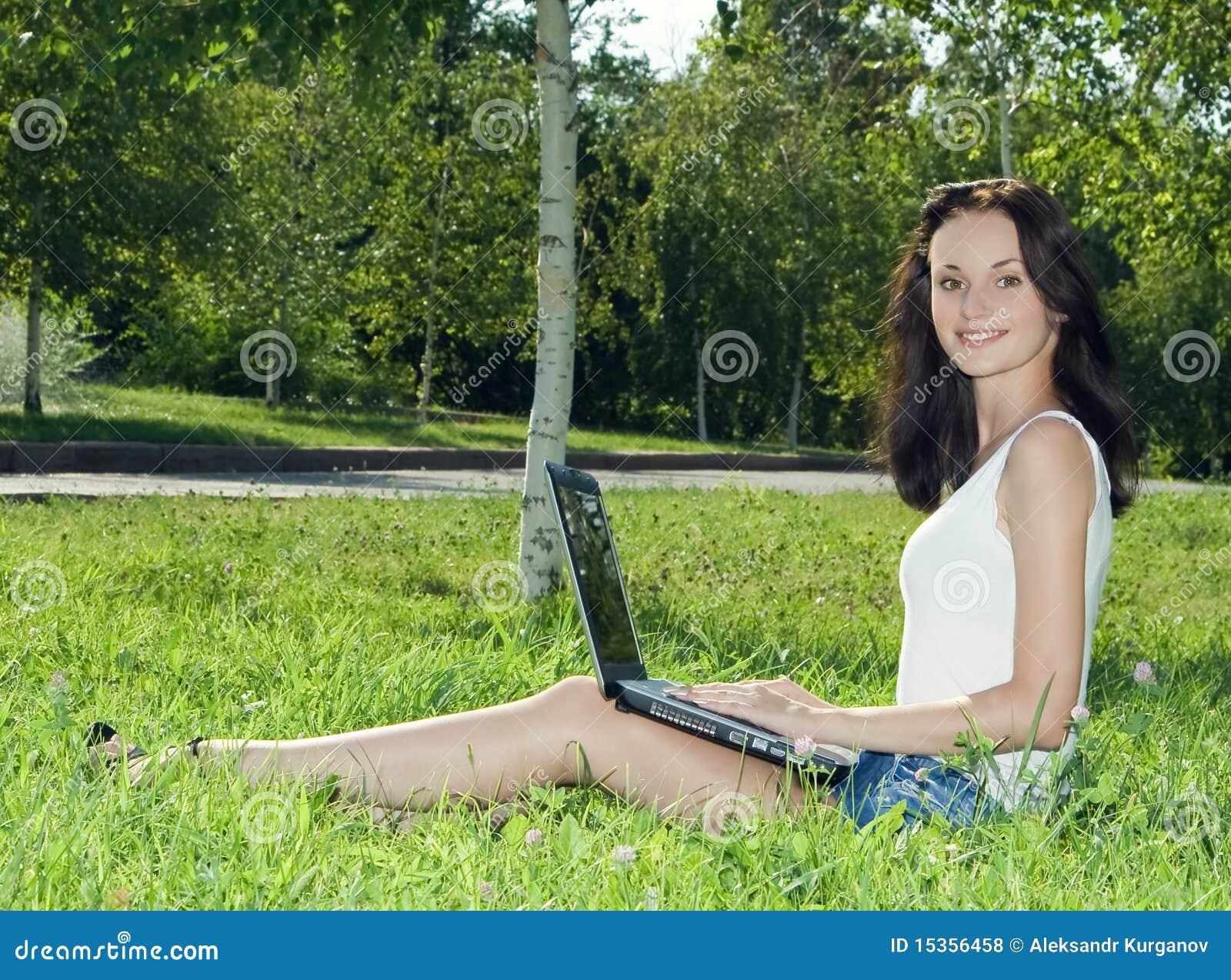 Belle femme en stationnement avec l ordinateur portatif