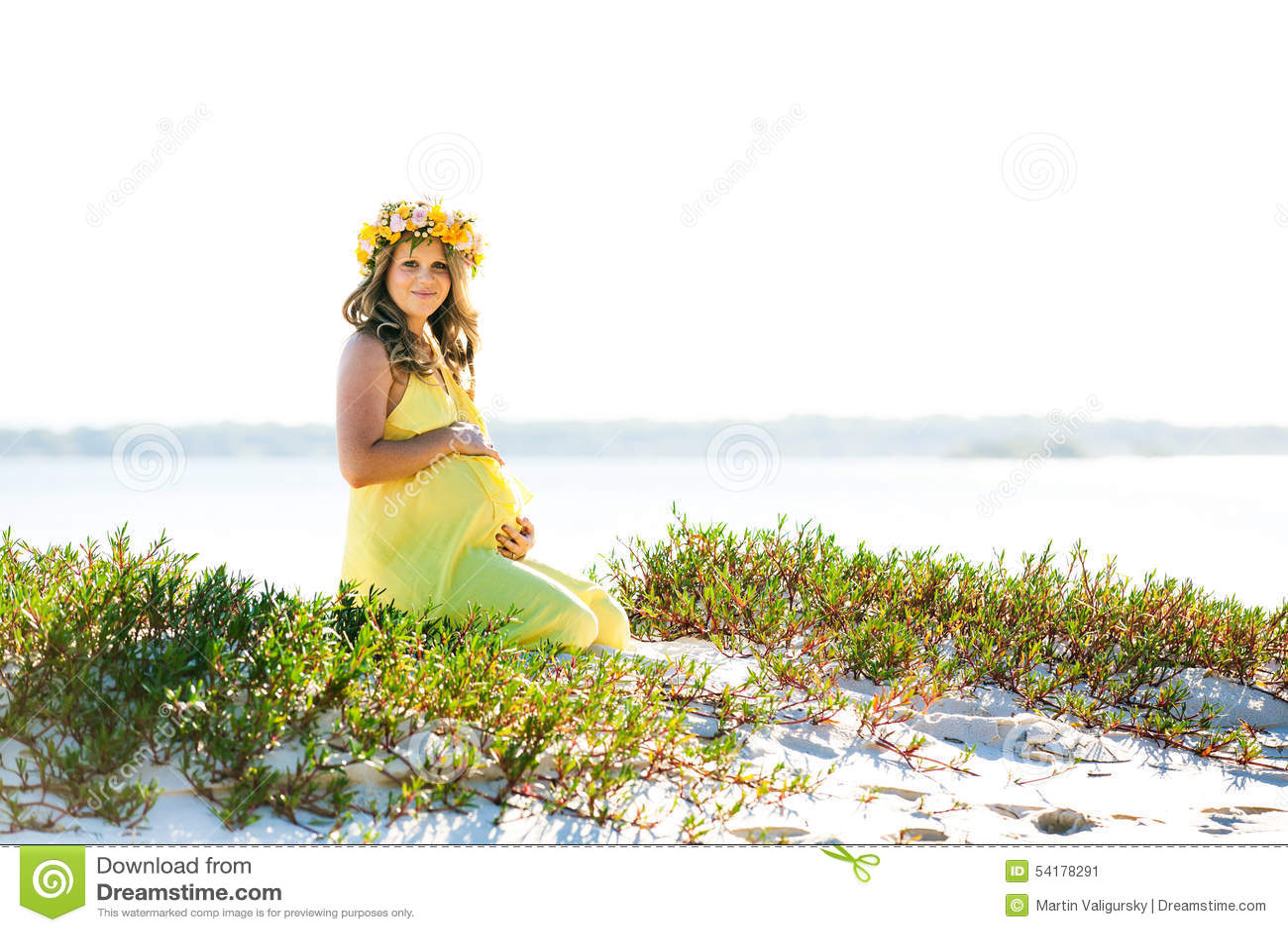 Belle femme enceinte de sourire avec des fleurs se reposant sur une plage