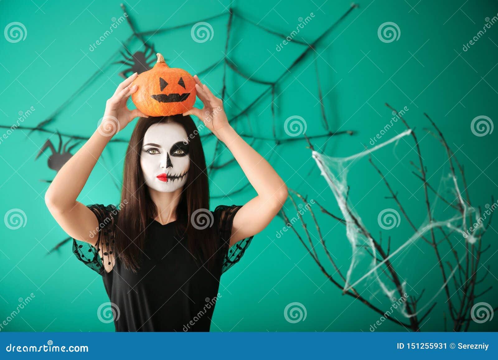 Belle femme habillée pour Halloween avec la position de potiron près du mur décoré