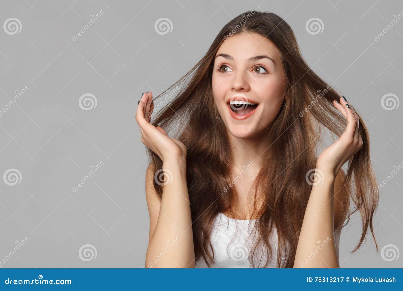 Belle femme heureuse étonnée regardant en longueur dans l excitation D isolement sur le fond gris