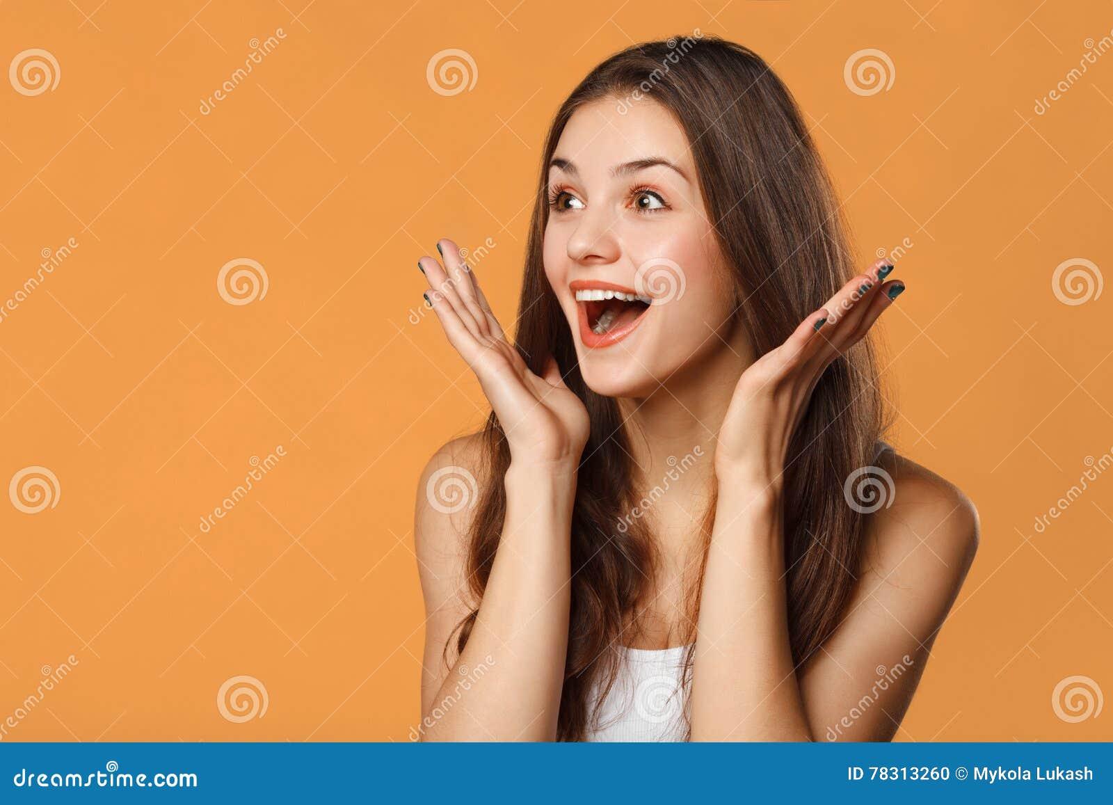 Belle femme heureuse étonnée regardant en longueur dans l excitation D isolement sur le fond orange