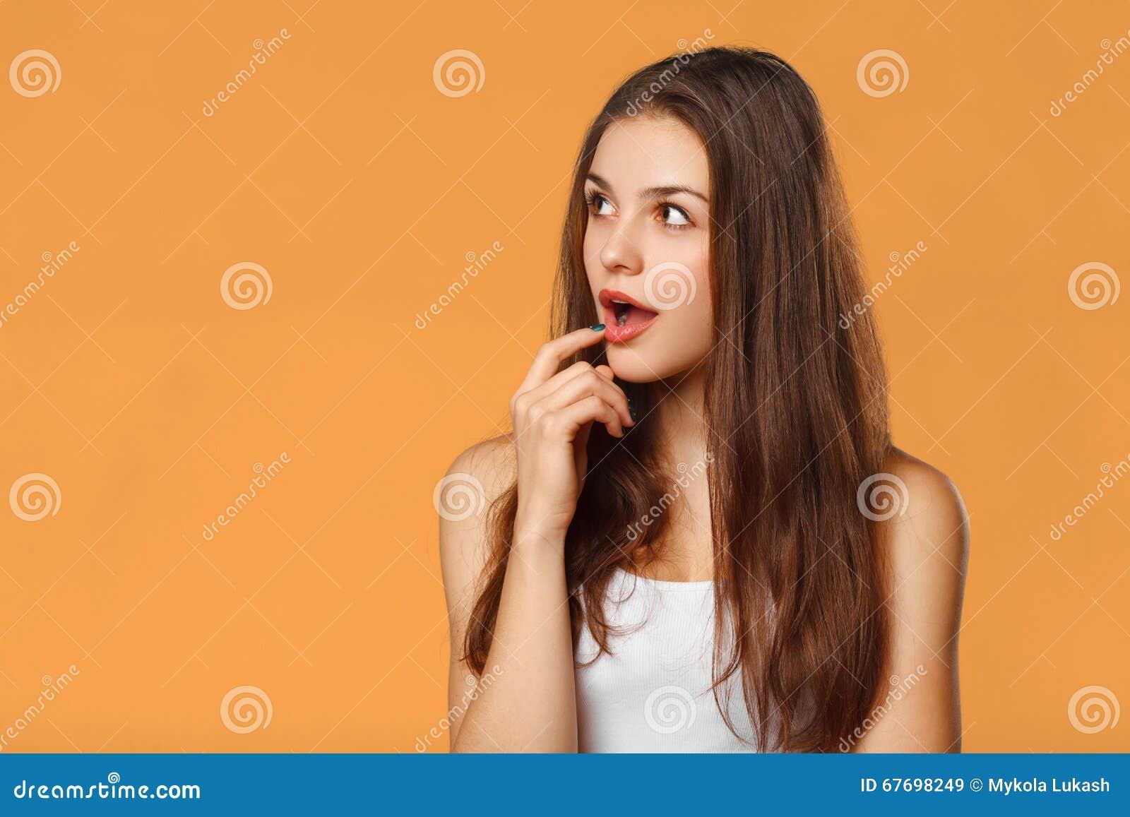 Belle femme heureuse étonnée regardant en longueur dans l excitation Sur le fond orange